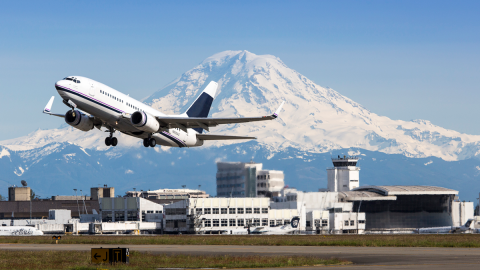 A jet airplane takes off from Sea-Tac Airport, with Mount Rainier in the background.