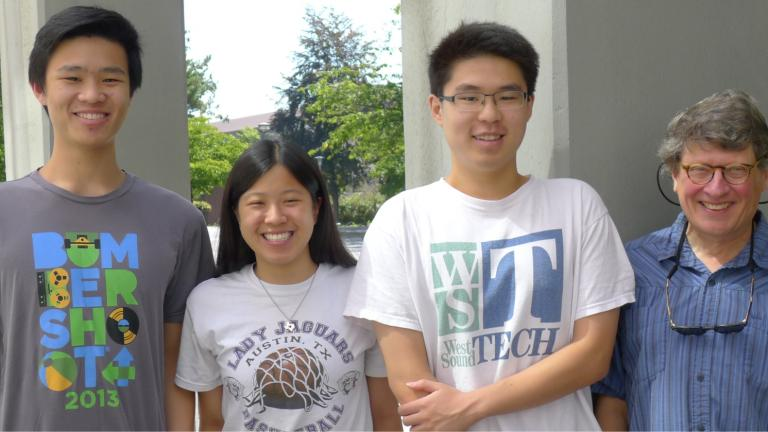 Dr. Monnat stands next to three former undergraduate lab assistants