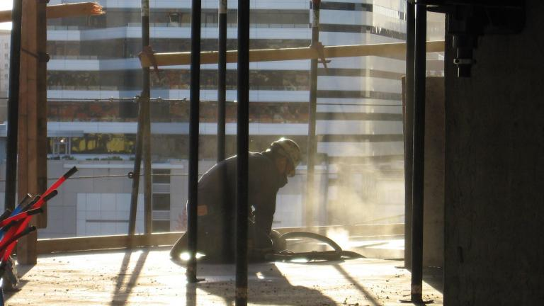 Construction worker sanding a floor with dust flying up