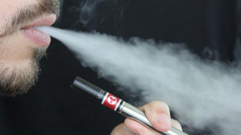 A man holds an e-cigarette while exhaling smoke.