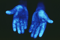Hands under black light.