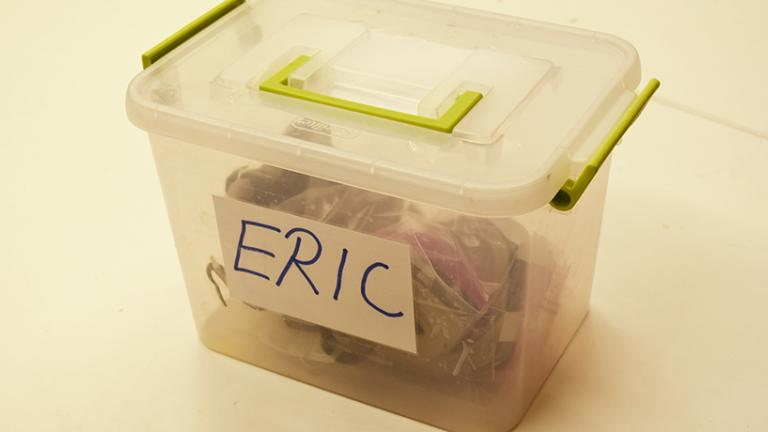 Image of plastic box with lid containing a respirator. Name on box reads, Eric