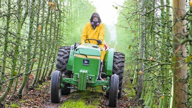 A man wearing an air mask drives a tractor through an orchard.