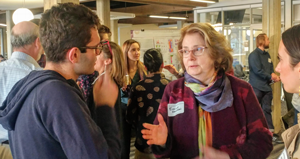 Faculty working with student at a poster event