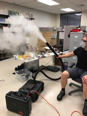 A seated researcher holds a fogging machine with a black tube emitting fog.