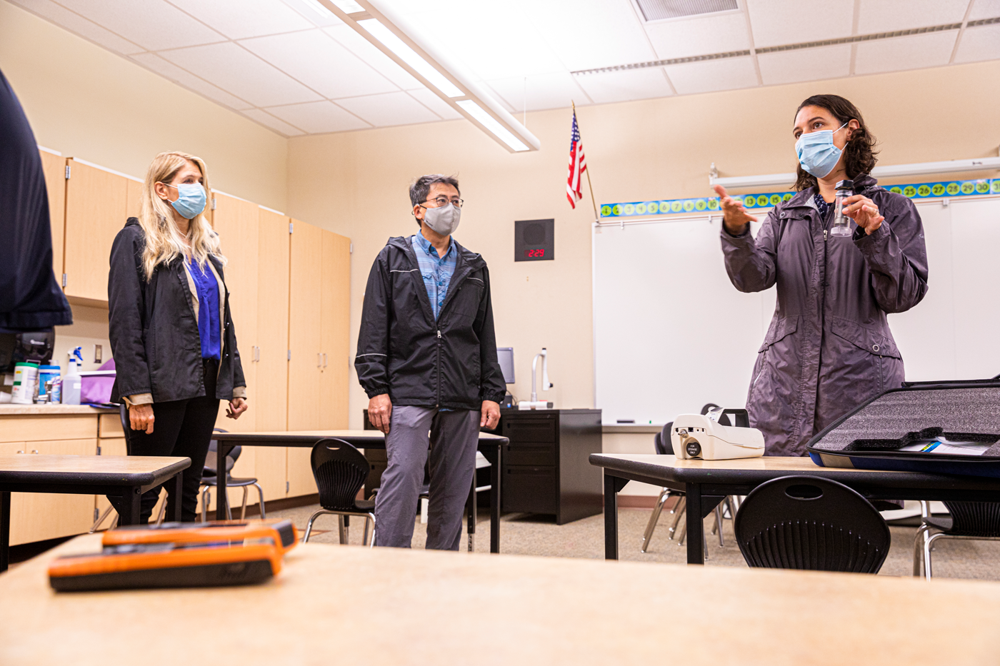Three people stand in a classroom. At right, Professor Elena Austin demonstrates air monitoring methods.