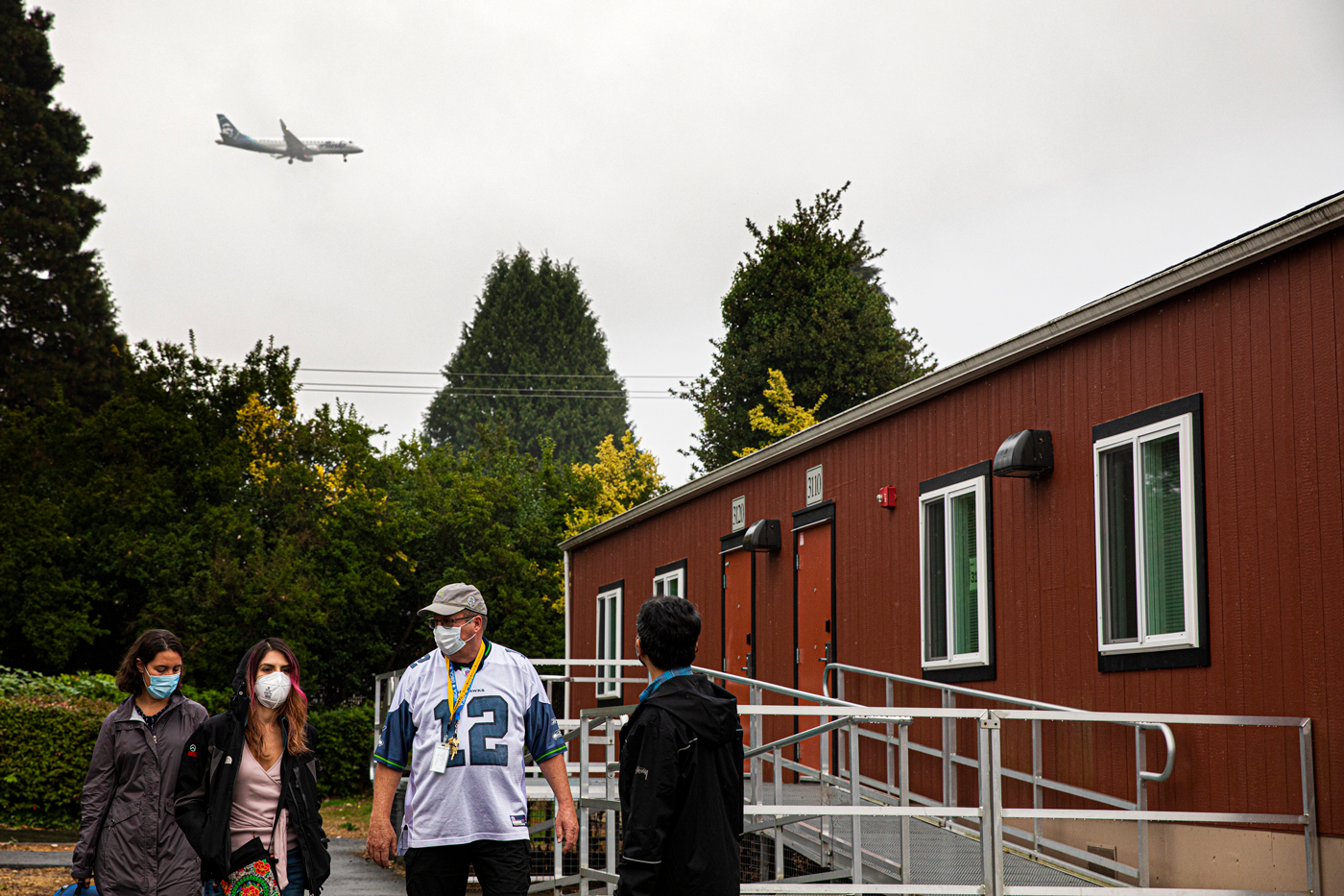 Four people stand outside a modular school building with a plane flying overhead.
