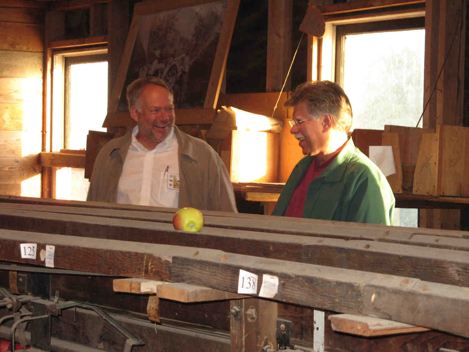 Two men talking in a barn near a pile of lumber with an apple sitting on top.