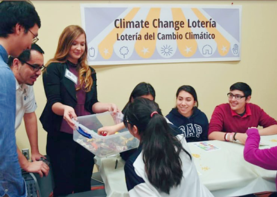 Drury hands out a box to a group of youth in a classroom playing a learning game about climate change.