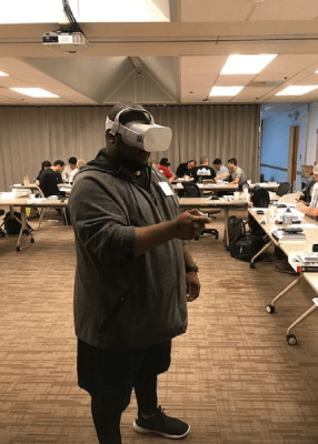 A person stands in a classroom using a virtual reality headset with people seated at tables in the background.