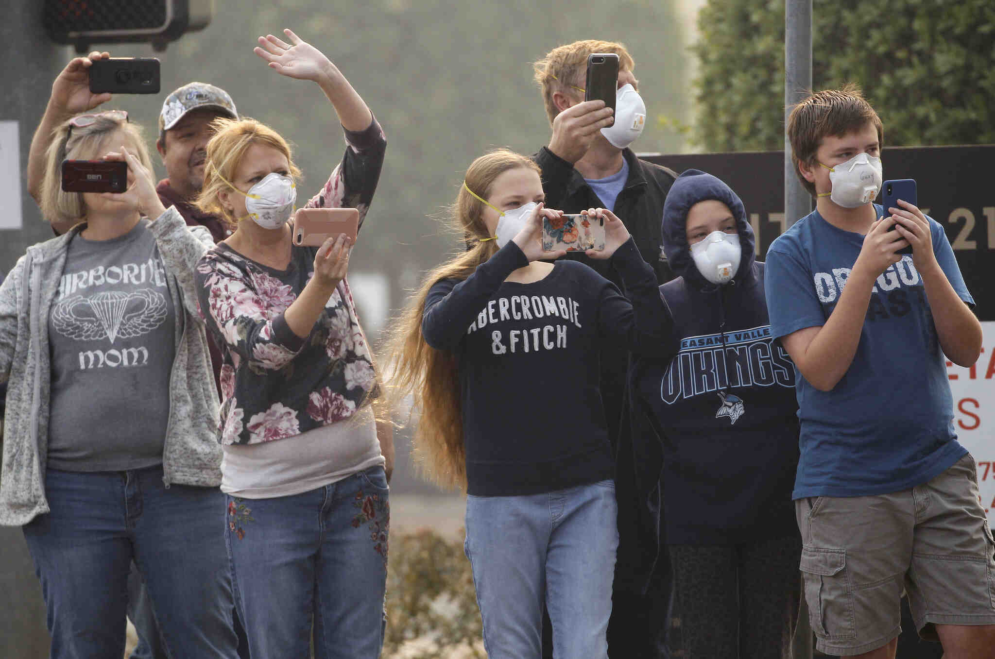 A group of people stand on a street wearing air masks and taking video on their cellphones.