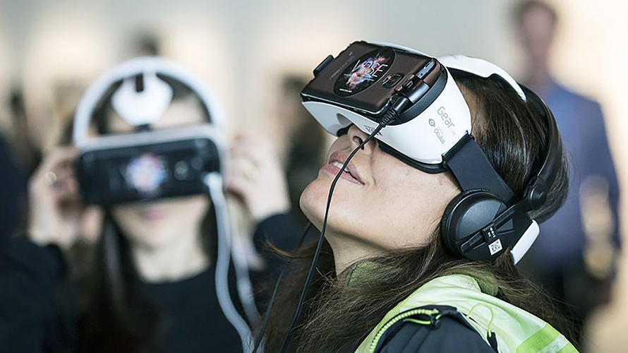 A woman wearing virtual reality goggles is looking up.