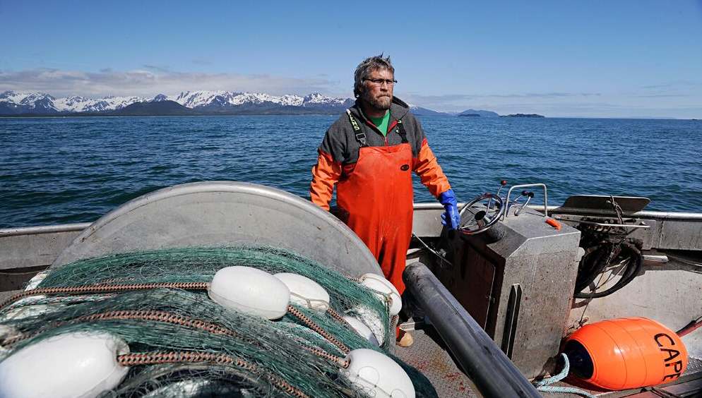 Fisherman stands on the deck of a silver, metal boat, mountains and the ocean behind him and fishing equipment around him.