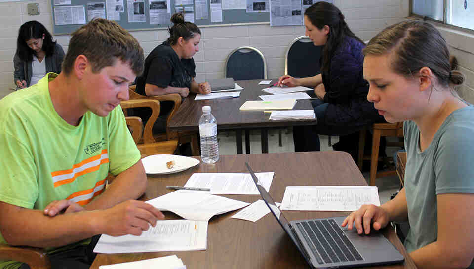 Students sit at tables interviewing construction workers.  In the foreground a female student with a laptop interviews a male construction worker with a packet of papers in front of him.