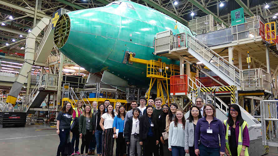 A group of DEOHS students, staff and faculty stand in front of an airplane under construction at a Boeing manufacturing facility.