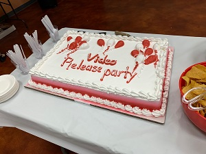 "A cake on a table with ""Video Release Party"" written in frosting."