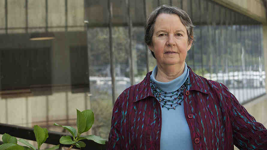 Professor Lianne Sheppard stands outside a University of Washington building next to a green plant.