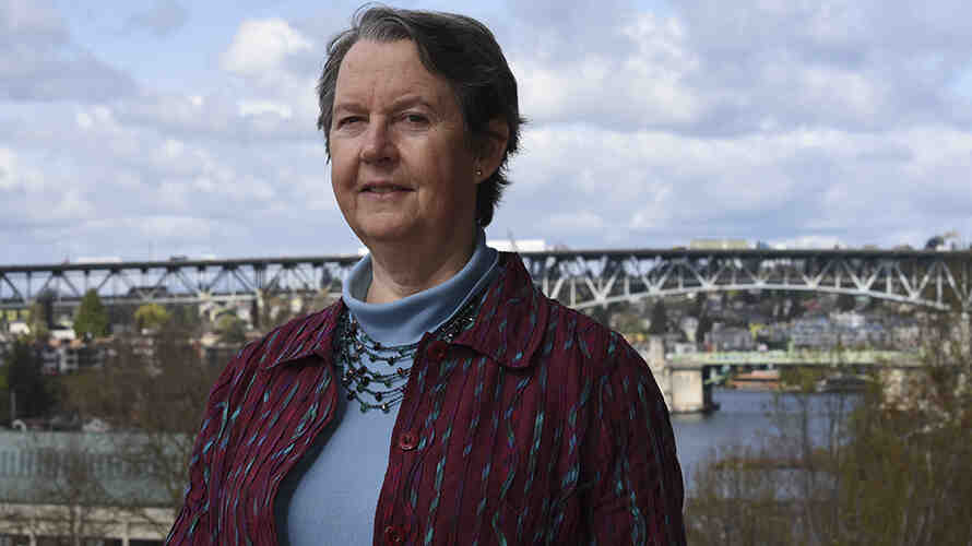 portrait of Lianne Sheppard standing outside.  A bridge with vehicles is in the background.  Photo by Sarah Fish.