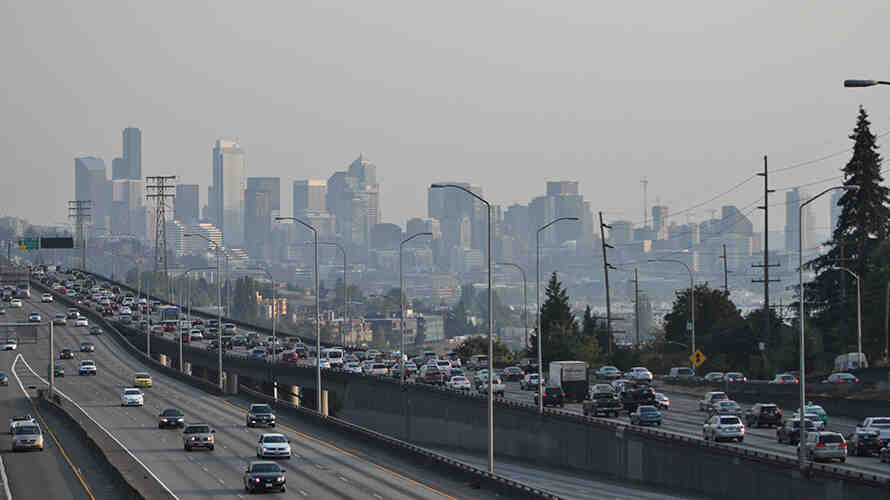 Photo of downtown seattle and interstate 5 with heavy traffic.  A haze of pollution obscures the buildings of downtown.