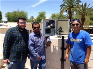 Three men stand in front of an air monitor that they installed in Imperial County, CA.