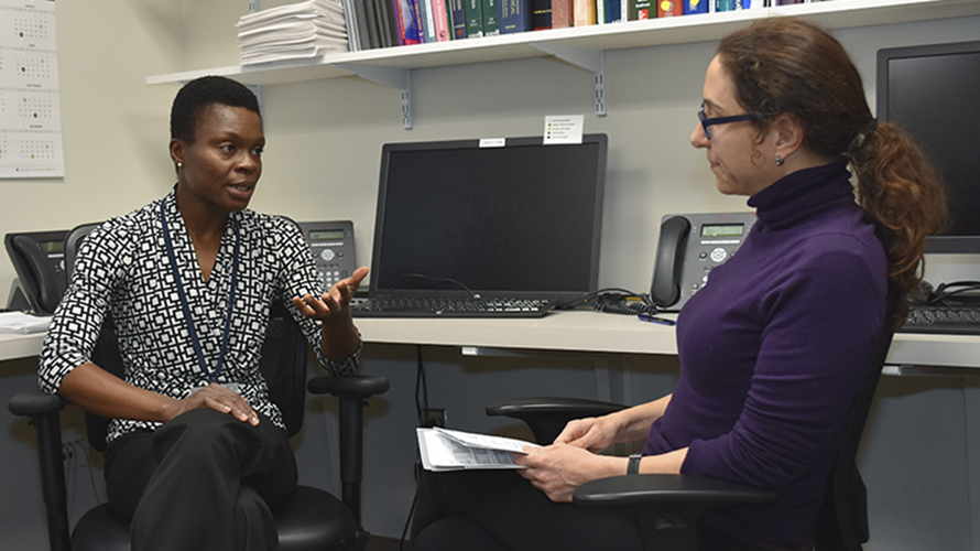Dr. Esi Nkyekyer discusses patient care with a medical fellow.