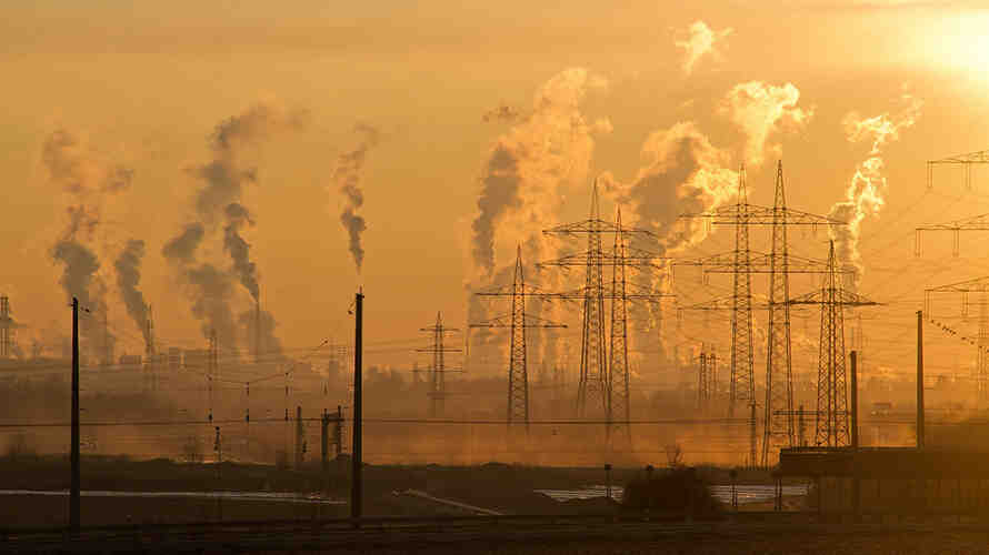 image of an industrial district encased in smog with many power lines running through.