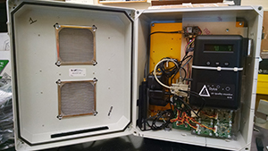 The inside of an air monitor.  White metal box with hinged opening that displays the wires inside.