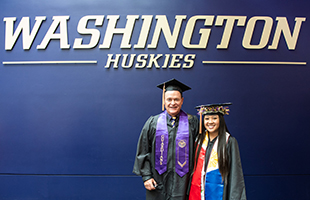 Castner and UW Senior Xamantha Curameng stand in graduation garb in front of a purple wall with light brown lettering that reads Washington Huskies.