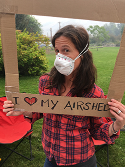 "A volunteer in a red plaid shirt with a filtering mask over her face poses with a cardboard frame that reads ""I love my airshed"", greenery in the background."