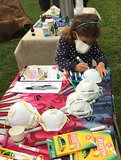 A little girl wearing an air filtering mask colors another mask with markers at a table.