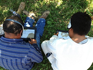 Two agricultural workers bent over tablets to take a survey while seated on grass.