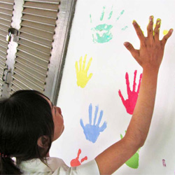 Elizabeth Wilcox - Children't Health - Child making a hand print on a paper with paint