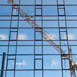Elliot Norwood - Continuing Education - Construction crane reflected in the windows of an office buildiing