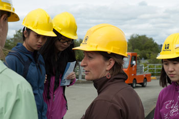 Teacher and students in hard hats on job site