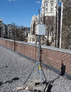 Picture of an air monitor box mounted on a pole on a roof.