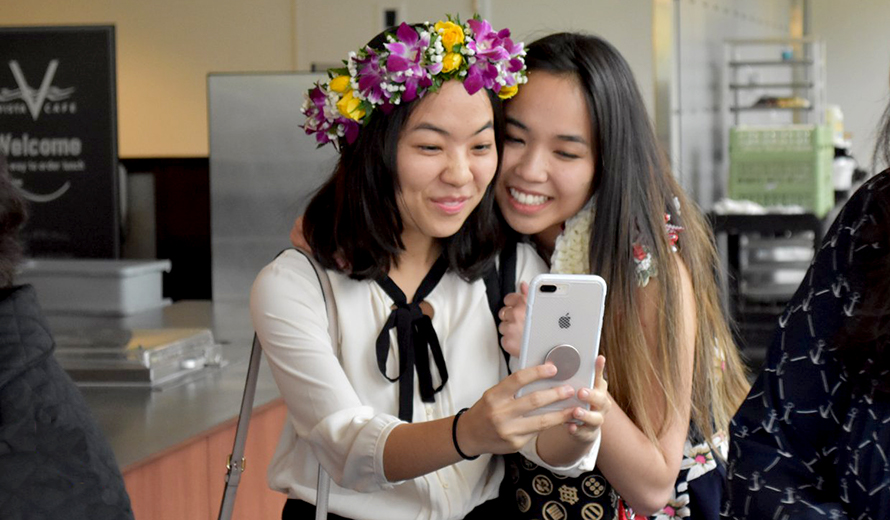 Two students take a selfie at the DEOHS graduation reception.