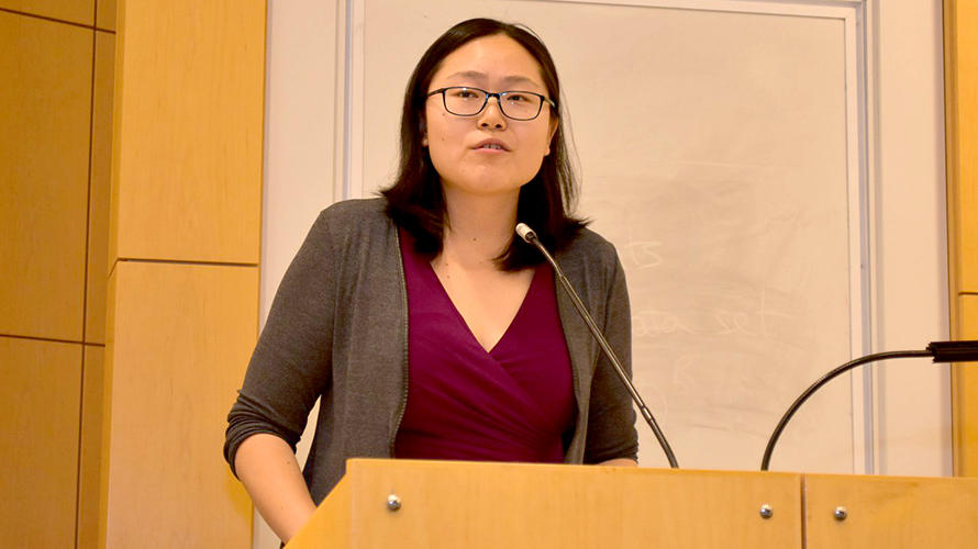 Connie Tzou speaking at a podium during the DEOHS graduation ceremony.