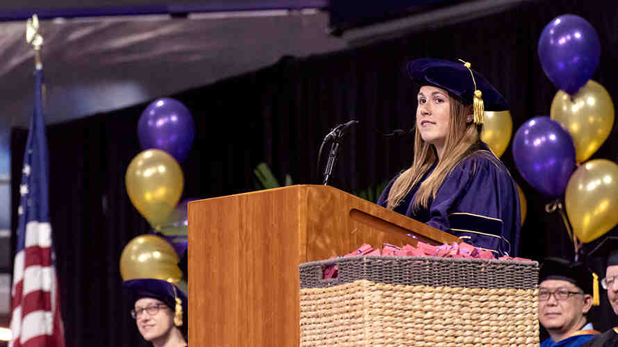 Miriam Caulkins speaking at a podium during the SPH graduation ceremony.