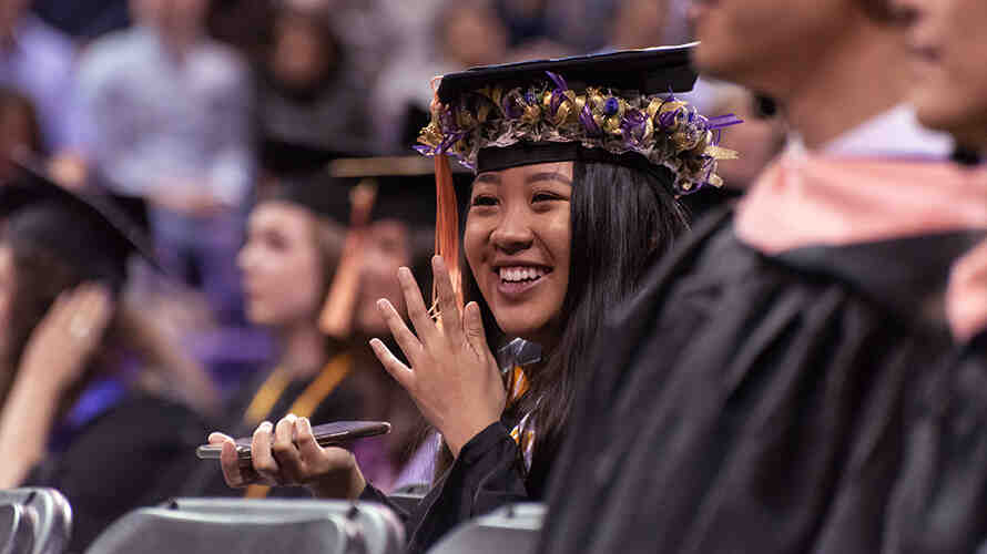Student sits waiting for to graduate in the SPH graduation ceremony.