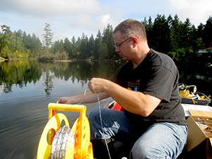 UW research technologist Corey King measures the water transparency of Lake Killarney.  He sits in a boat with the lake and trees int he background, working with a large spool of rope.  Photo: James Gawel.