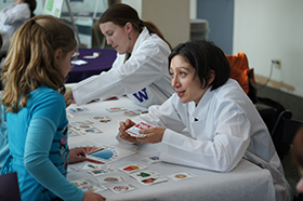 A DEOHS student talks with a child across a table at the Paws-on Science event in the Pacific Science Center.