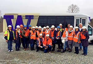 The Mongolian delegation stands with members of DEOHS Continuing Education program in front of a bus wearing construction site safety gear.