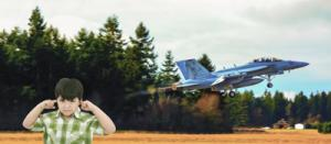 Boy covering his ears next to a jet taking off.