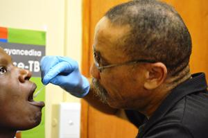 A medical staffer in Cape Town, South Africa, collects a patient's swab sample.