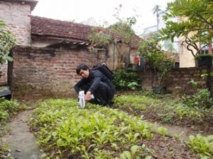 Nguyên Khac Hoài Nam tests a vegetable garden in the village of Dong Mai using an XRF elemental analyzer.