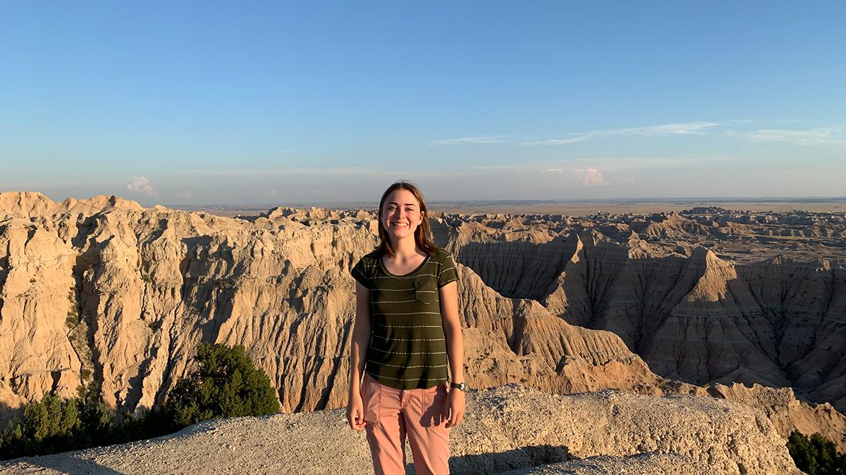 UW senior Natalie Peterson standing in front of a canyon in the Badlands.