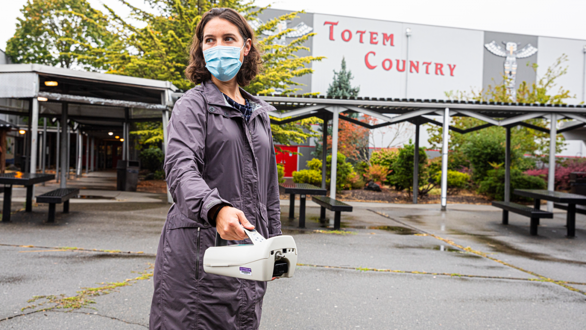 DEOHS Professor Elena Austin stands in a parking lot outside a school holding an air monitoring instrument.