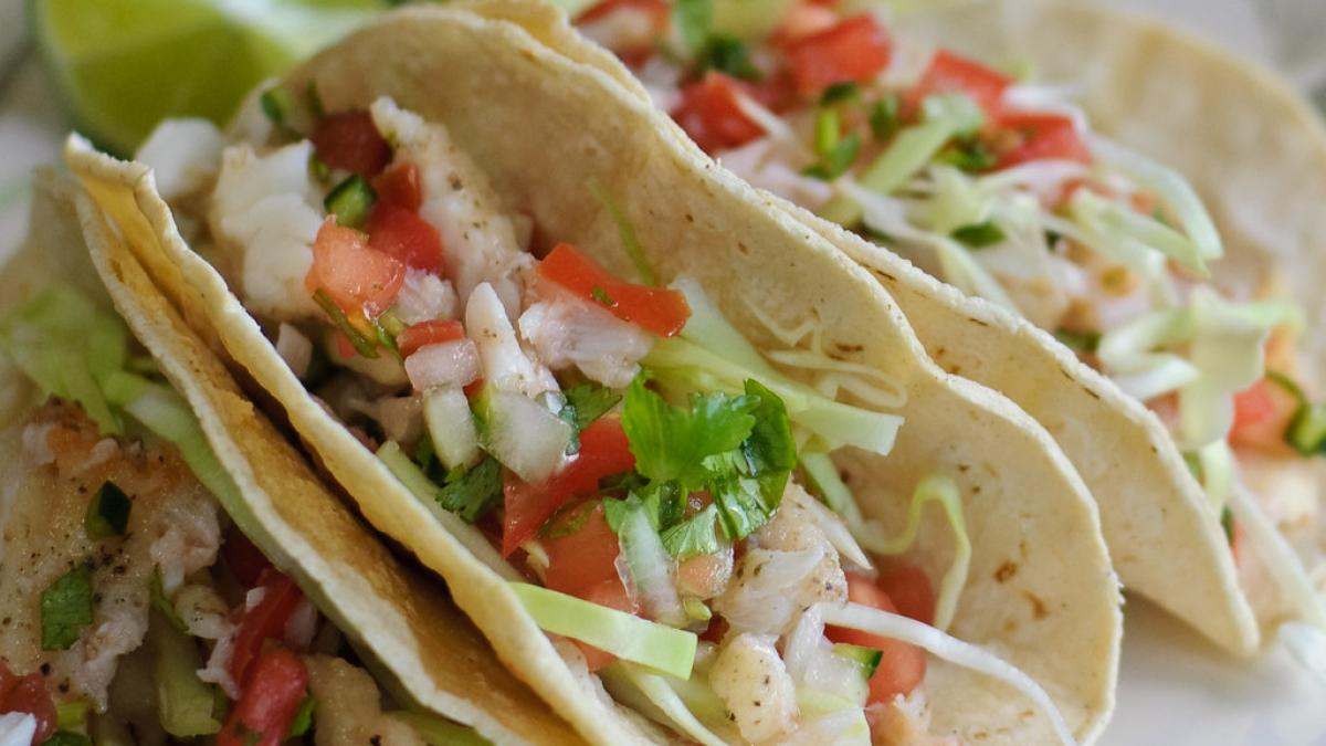 A serving of fish tacos with fresh vegetables.