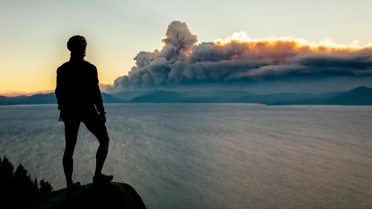 A woman in a bike helmet looks out over a lake toward wildfire smoke in the distance