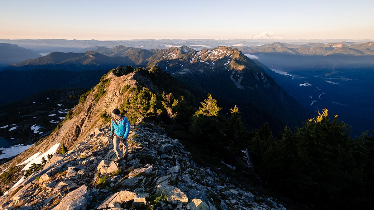 Panoramic photo of person hiking on mountain peaks. Photo by Soren Johnson.